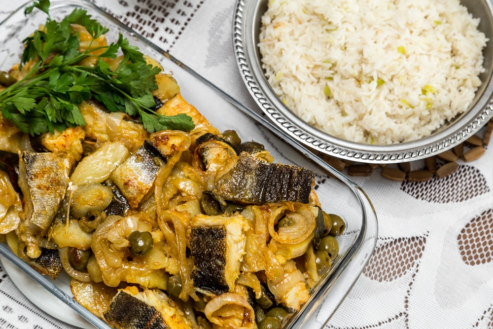 Delicious and traditional portuguese codfish with potatoes and a plate with rice
