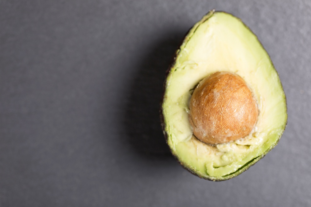 Exotic fresh avocado on black slate with copy space