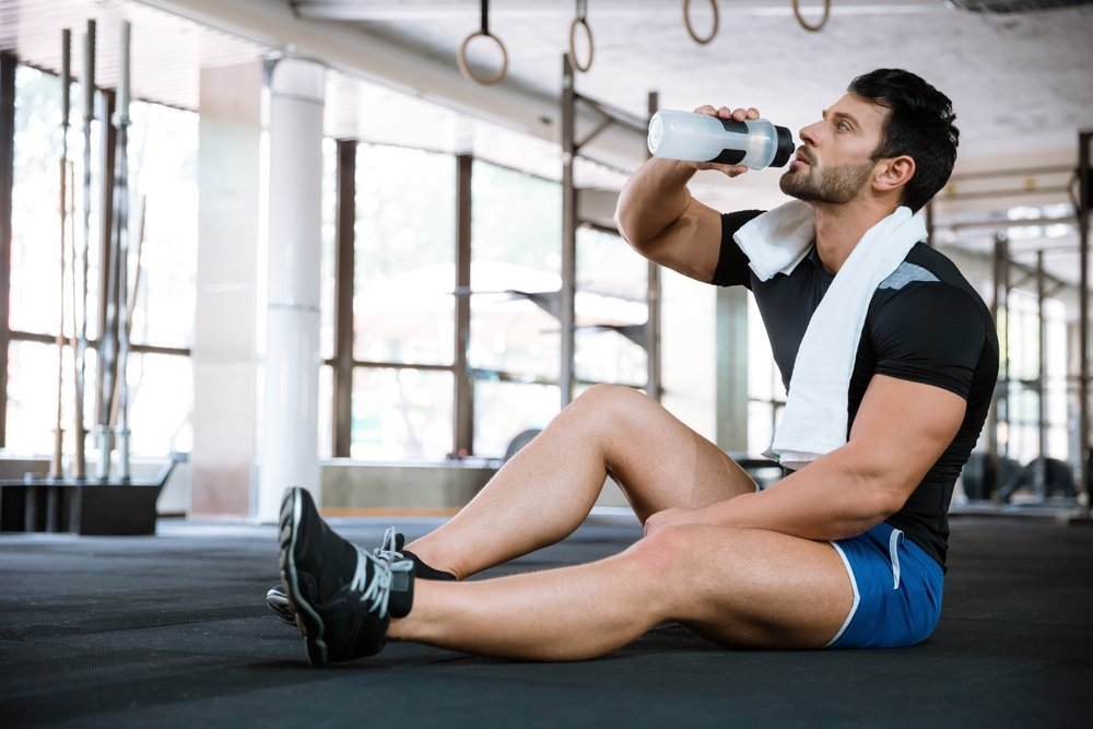 Fitness man wearing blue shorts and black t-shirt sitting on the floor and drinking water