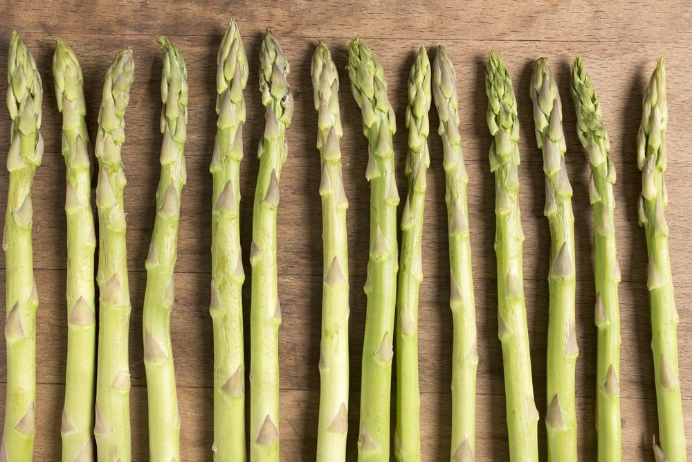 Fresh raw asparagus on a wooden kitchen work surface