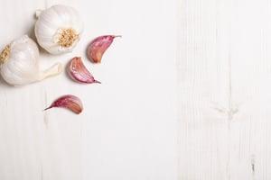 Fresh raw garlic on a light wooden kitchen work surface