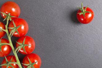 Fresh ripe tomatoes on black slate