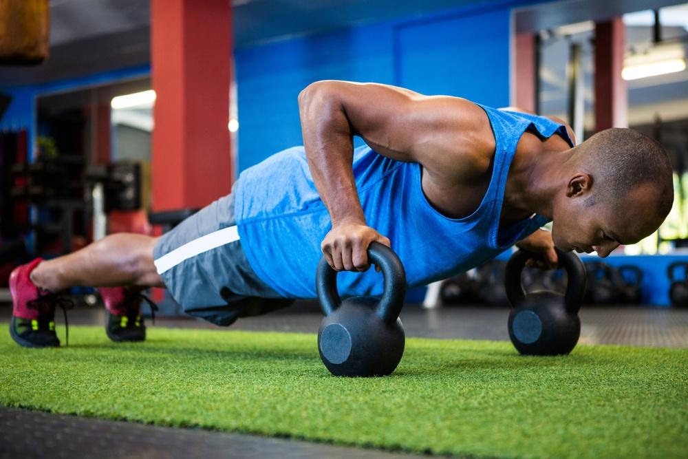 Full length of male athlete doing push-ups with kettlebells in fitness studio