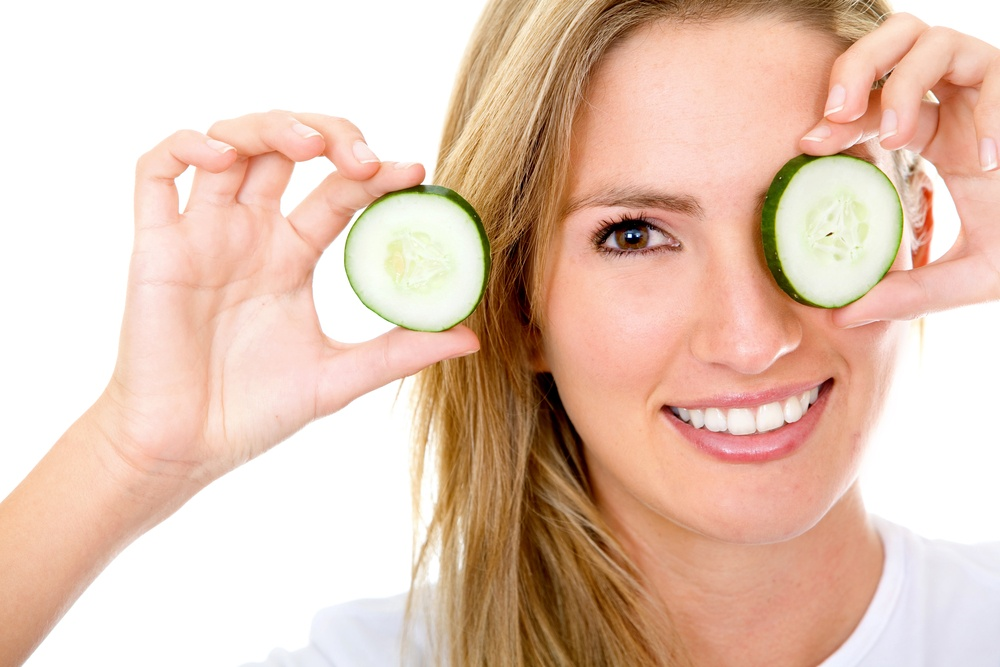 Woman with a slice of cucumber in her eye - isolated over a white background